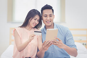Couple looking at table holding credit card