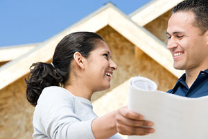 Couple looking at home plans in front of partial construction